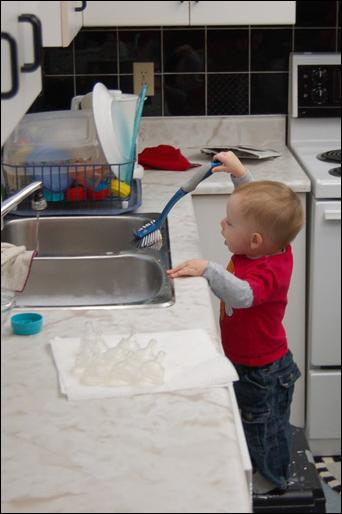 John Thomas scrubbing the kitchen sink