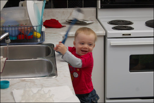 John Thomas at the kitchen sink with a big smile waving the scrubber around